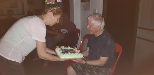 Susie bringing a cake to Bill.