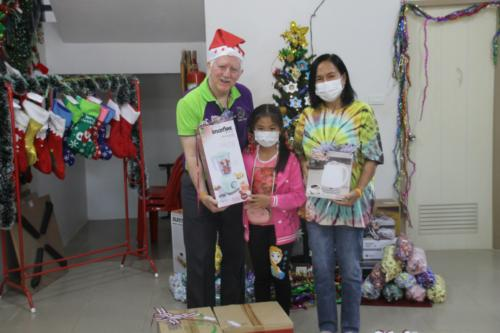 Bill giving gifts from Mountains Christian College to Nee and granddaughter.