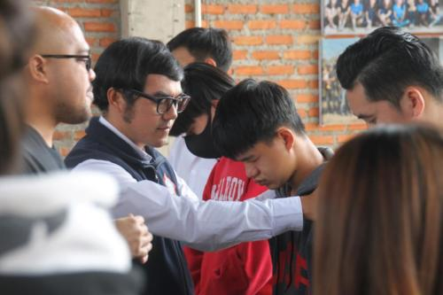 Mark and Asanee praying with boys.