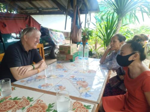 Bill, Nong's mom, and Nong discussing prayer needs.